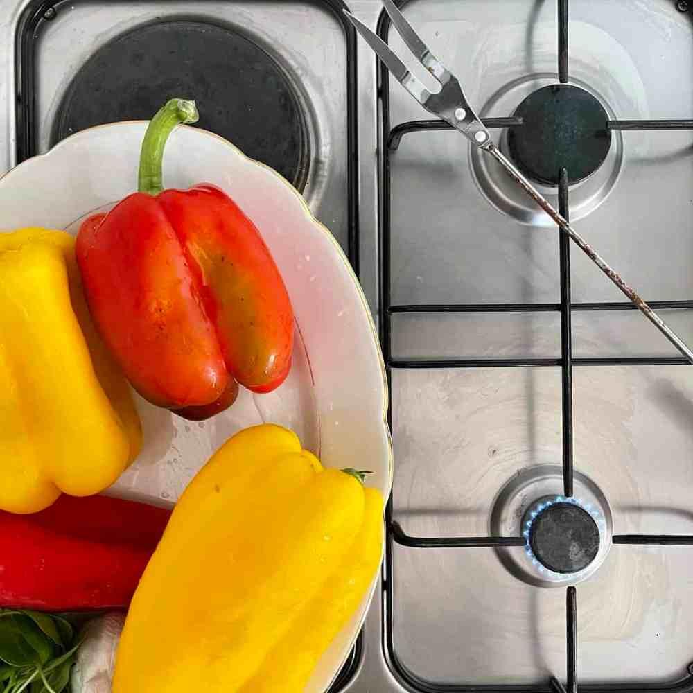 Mit einer feuerfesten Zange/Gabel die Paprika über die Gasflamme halten.