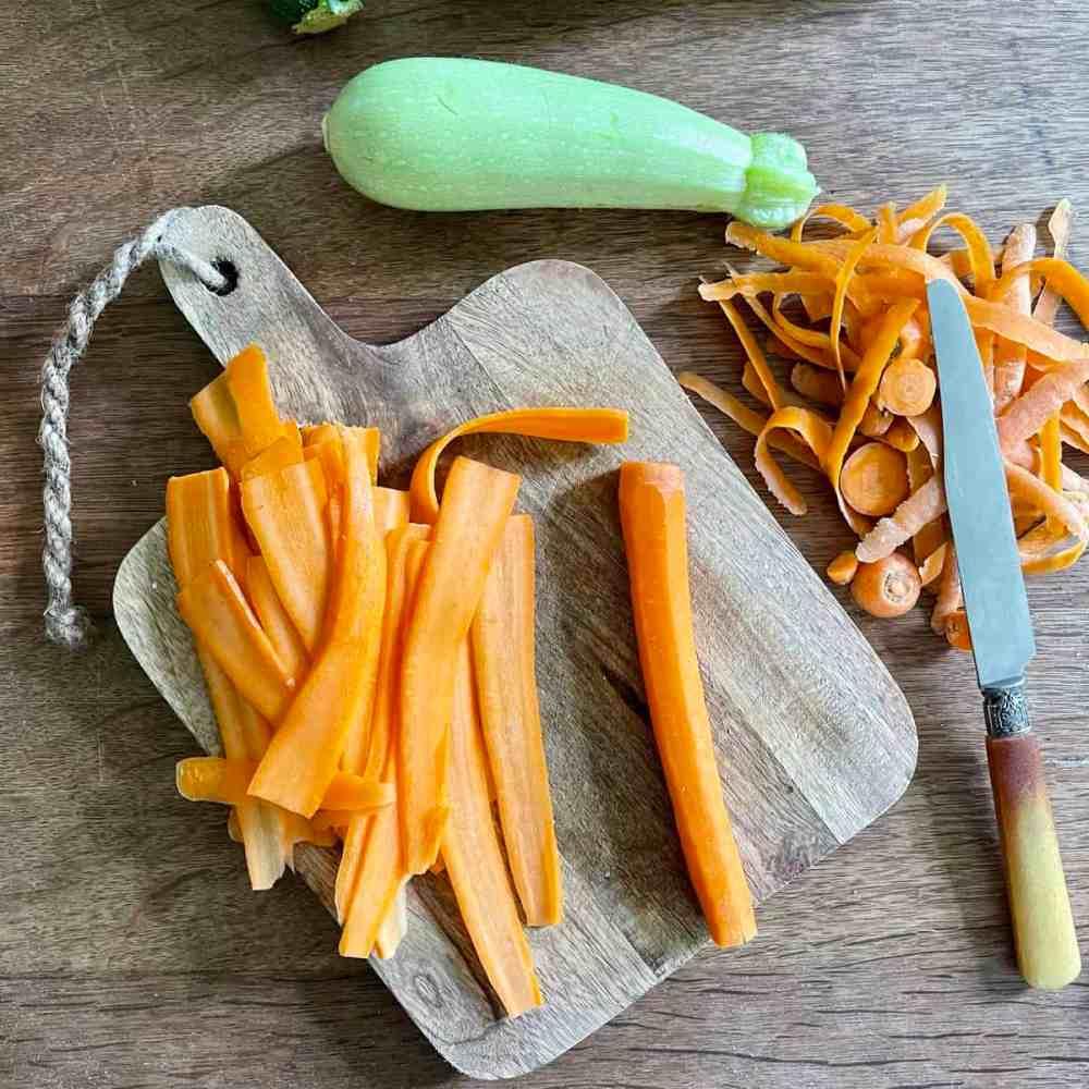 Die Karotten und Zucchini putzen und in feine Streifen schneiden.