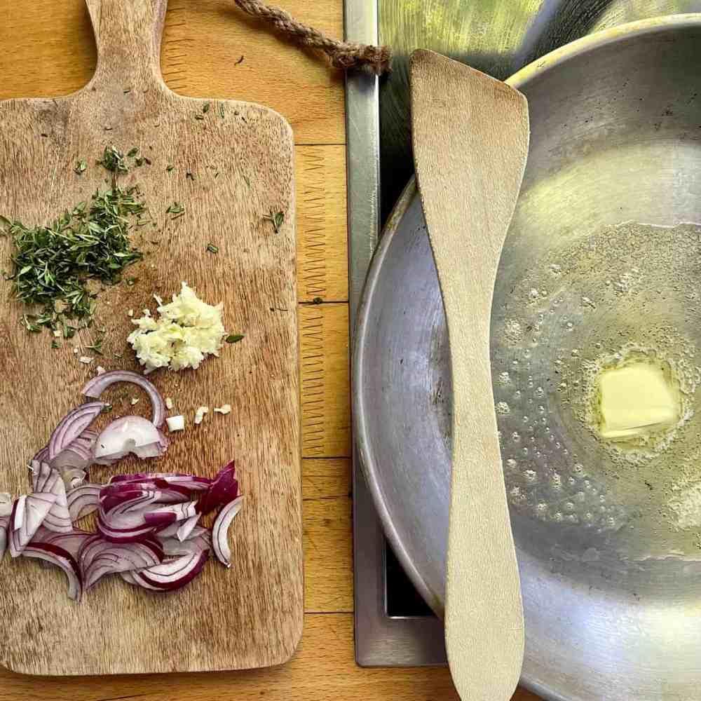 Zwiebeln und Knoblauch in einer Pfanne mit Butter andünsten.