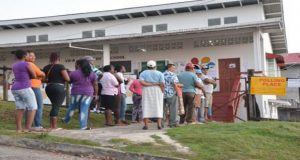 Early birds: These persons gathered at the Hill View Polling Station were anxiously awaiting the opening of poll