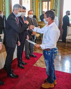 Vidal Rivas, uno de los beneficiarios del proyecto, recibiendo su título de propiedad de la mano del Presidente de la República Mario Abdo Benítez.