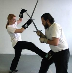Zoe Chandler kicks Miika in the nuts: for The Swordsman's Companion.