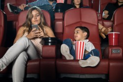 mom on phone in movie theater with her son