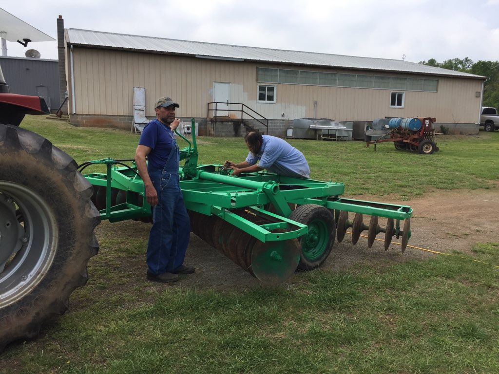 Thunder Lane and Jim Smith ready a disk to prepare land for planting at The Carver Center. They belong to the Black Farmers of America.