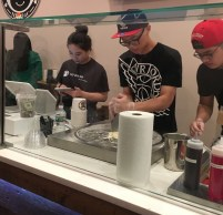 Employees ring up customers and start to prepare their rolled ice cream dishes.