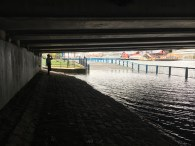 One observer takes a coffee break alongside the rushing water under a bridge in South Boston. Though the tides are mainly a spectacle now, some coastal neighborhoods are already being impacted by rising sea levels.