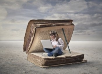 Image of woman using laptop inside giant book