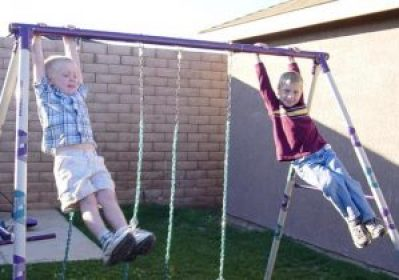 boys hanging from swing set