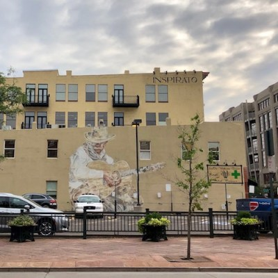 Tan, four-story building painted with mural of a man in a cowboy hat playing guitar
