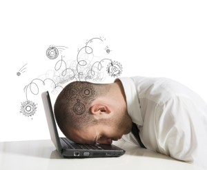 man with head facedown on laptop with squiggles drawn over his head