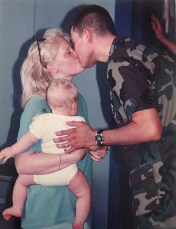 Gwen holding a baby and kissing her husband who's wearing Air Force camouflage/BDUs