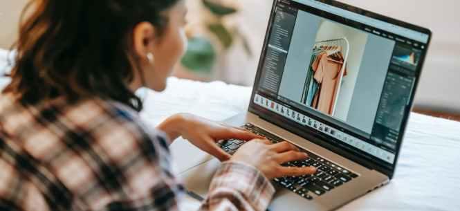 crop ethnic freelancer retouching photo on laptop at home
