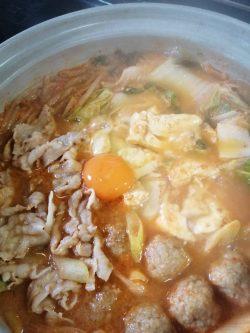 スンドゥブチゲキムチ味豆腐の上に卵を割り入れる