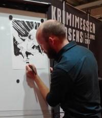 Tom Kristensen tegner på Krimimessens stand under Bogforum 2016