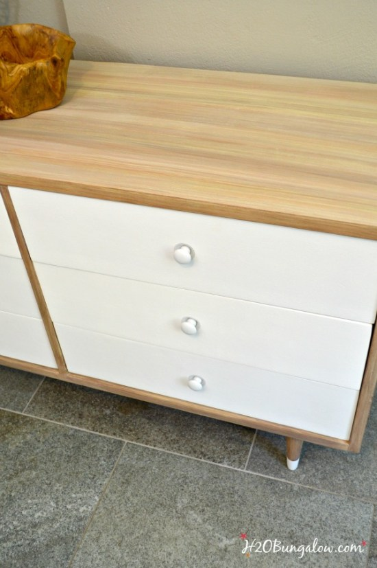 Mid Century Modern dresser makeover brought a ruined old dresser back to a beautiful piece of furniture that looks fabulous. I used an easy process of faux painting a wood slab look on the body. Sharing an easy tutorial any level of DIYer can follow. This post links to many more fabulous storage and organization furniture makeovers from the Themed Furniture Group H2OBungalow.com