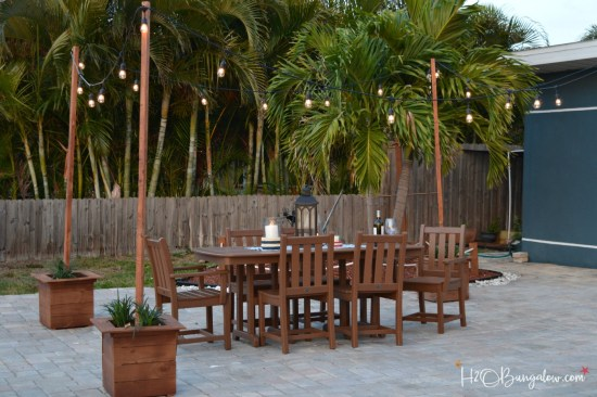 DIY outdoor string lights on poles tutorial. Holds up in gusty wind and weather, leave your string lights out year round for beautiful night ambiance. Find this and over 450 more home improvement and home decor DIY tutorials on H2OBungalow.com