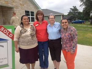 Debbie Eller, from City of College Station, celebrate the home dedication with the Sanchez family