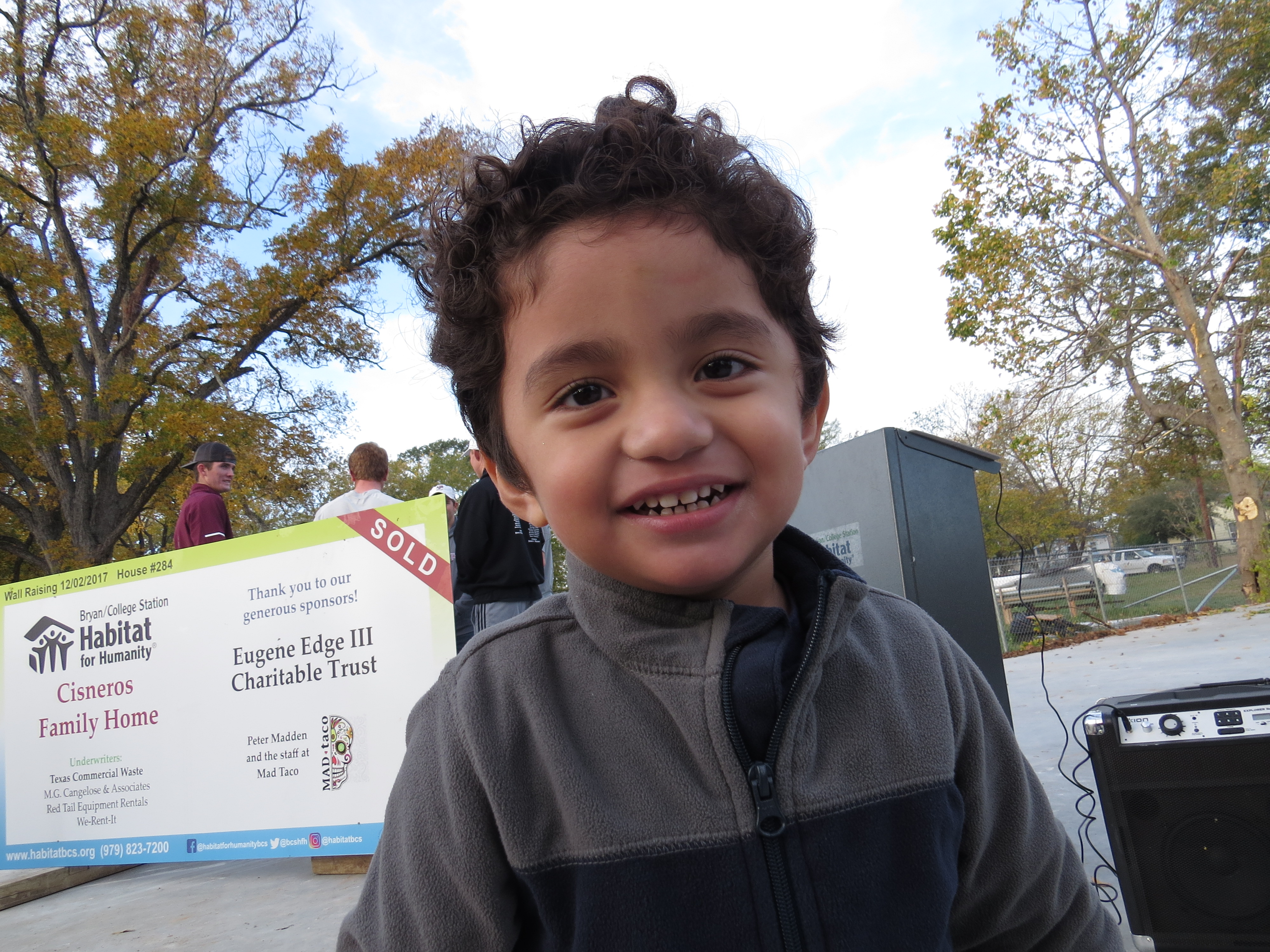 Cisneros' son smiles in front of their future Habitat for Humanity home.