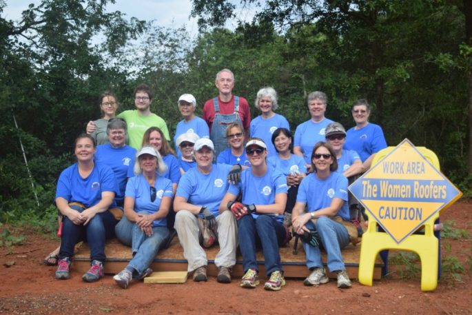 Women Roofers complete their 100th roof in Spindale in Rutherford County. The house is part of the SECU Mountains to the Sea Challenge, Left to right, front row: Beth Archer, Jane Alexander Bell, Lori Herrick, Caroline Blanton, Lynn Blanton; second row: Emily Moose, Jennifer Moose Moore, Susie Kernodle, Myra King, Beth Stover, Terry Honeycut; back row: Jade Thompson, Scott Herrick, Donna Ohmstead, Billy Honeycutt, Helen Rogers, Nell Perry Bovender, Janet Jolly.