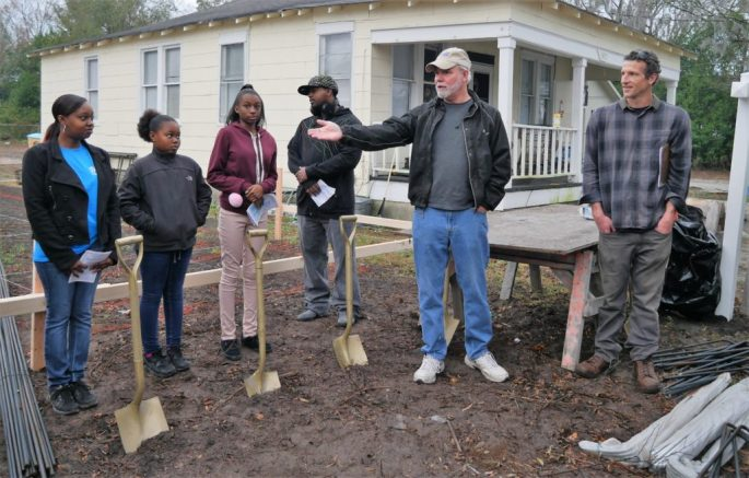 Steve Spain, executive director of Cape Fear Habitat for Humanity, introduces Alicia Zenon and her daughters Destiny and Shaniah Morris just before the groundbreaking.