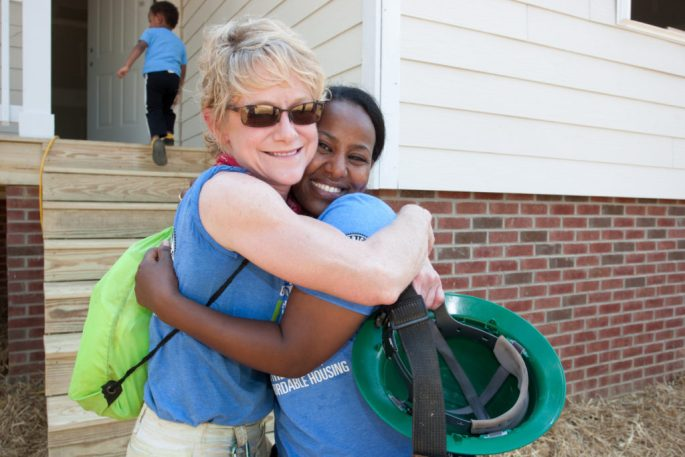 HFH Wake County volunteer Lisa Hughet hugs home owner Tarik Araia in front of her new home after the closing ceremony of the annual Habitat for Humanity AmeriCorps Build-a-Thon being held in Wake County, North Carolina on Friday, May 27, 2016. Photo by Gregg Pachkowski/Habitat for Humanity International