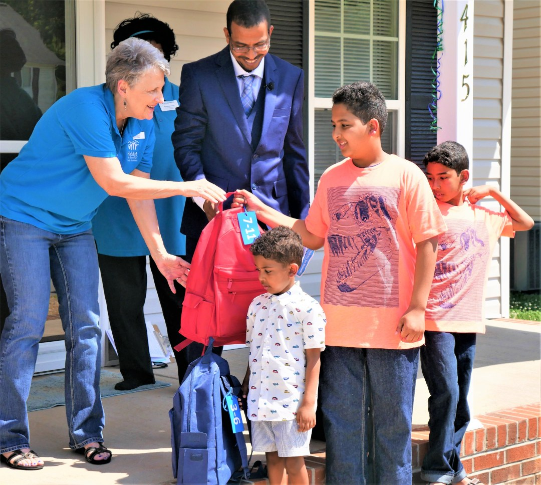 Ramona Carl, director of homeowner services for Habitat for Humanity of Greater Greensboro, hands out backpacks to the children of Abdelrhman Elbahi and Abir Mohammed.