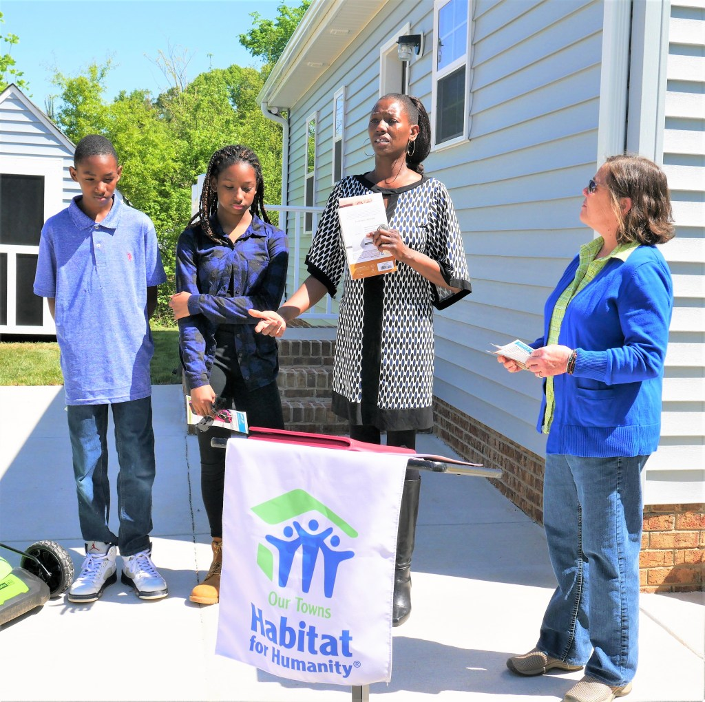 After offering a house blessing and prayer, Tiffani Irwin, right, construction manager for Our Towns Habitat for Humanity, listens as Perryrease Stinson and her son Michael, 13, and daughter Mahkia, 14, thank all of the people who helped to build her new home.