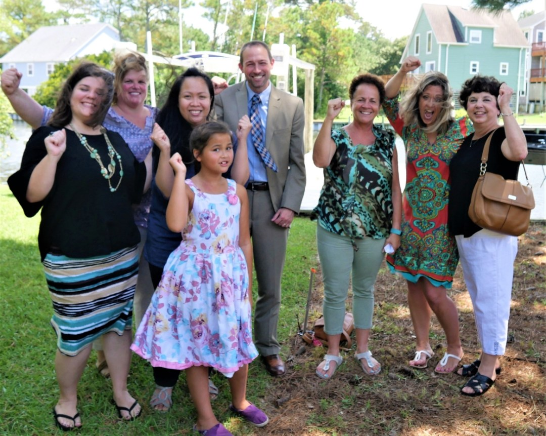 With representatives of the local SECU offices, Pat and Savannah Moncur lead a fist-pump of appreciation.