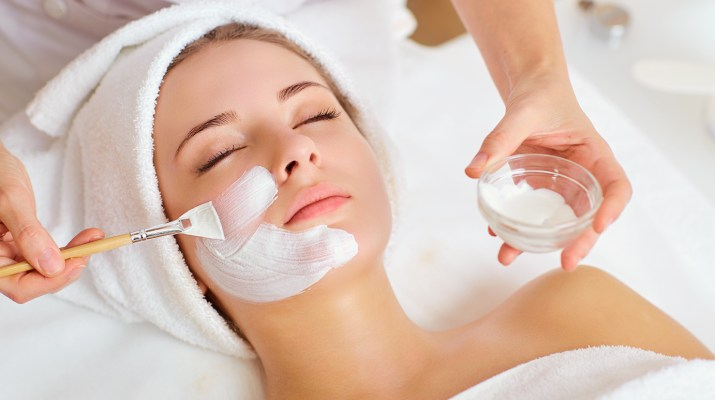 Woman getting face mask brushed on at spa