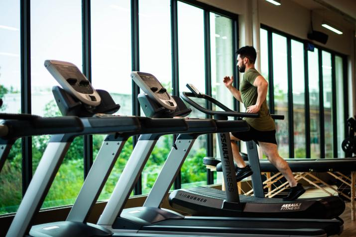 Photo of man running on treadmill in front of a line of windows