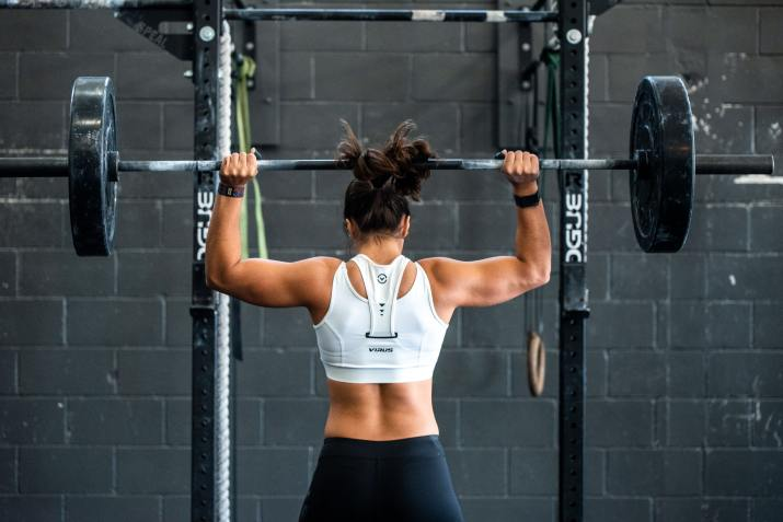 Photo of woman lifting barbell off a squat rack