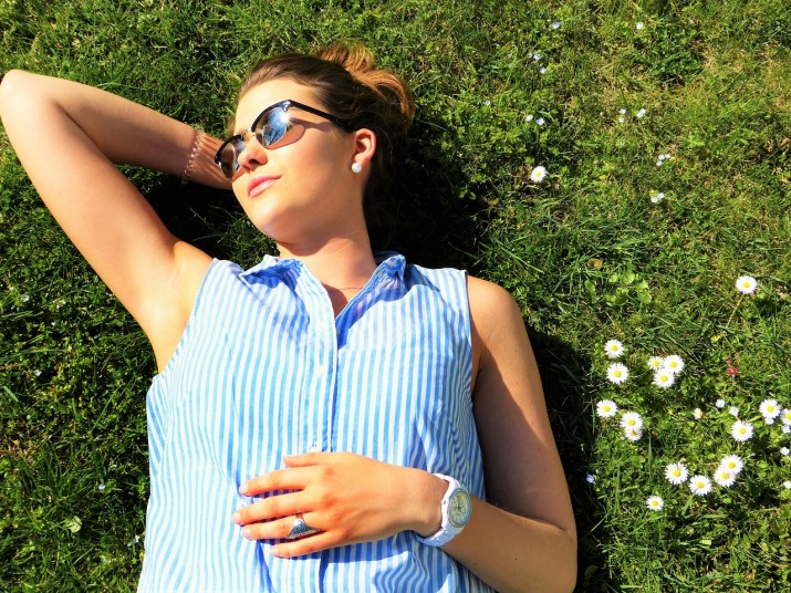 Woman laying down in grass wearing sunglasses, basking in the sun.