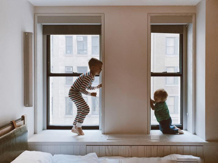 Two children playing on window sills