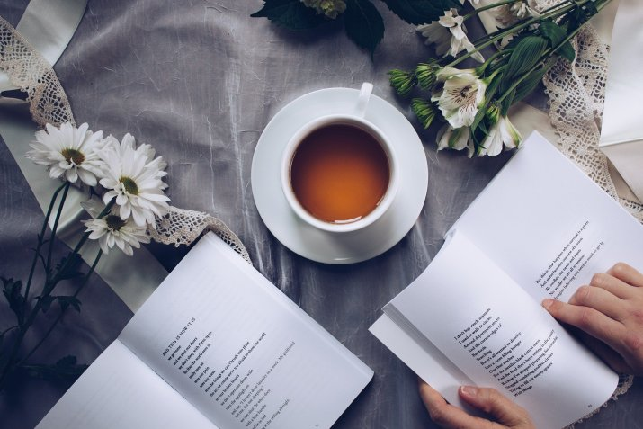 Flat lay photo of open books of poems next to a cup of tea and white flowers