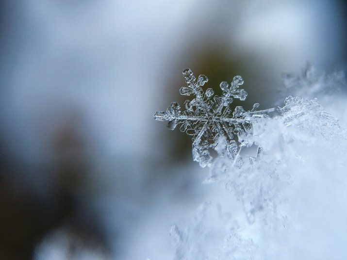 Close-up photo of an individual snowflake attached to a larger collective of snow.
