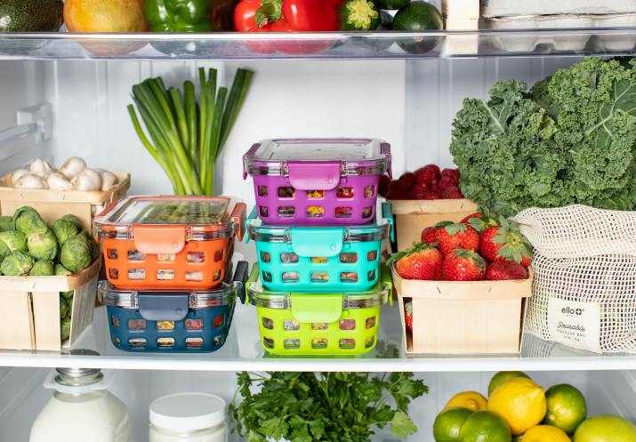 Refrigerator shelves stocked with kale, strawberries, brussels sprouts, and colorful containers of meal-prepped food