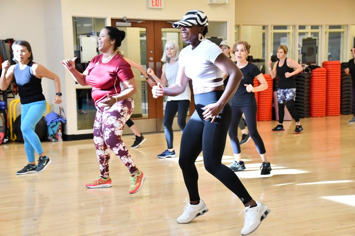 Mus leading a group of smiling women during a Zumba class