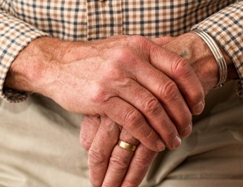 Close-up of senior man with hands together on top of cane