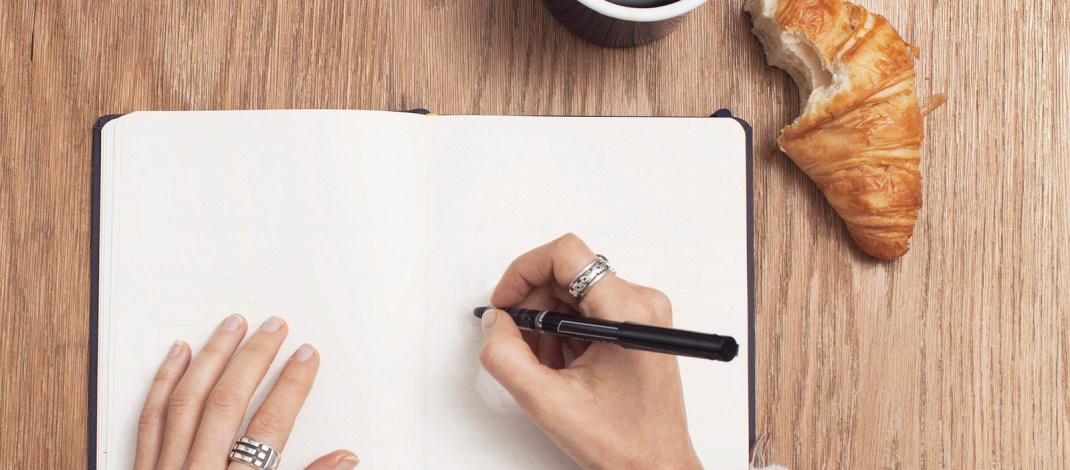 Woman getting ready to write in open notebook with coffee and croissant