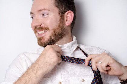 クリーニングしたばかりのネクタイを締める男性
