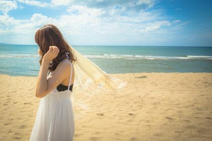 海の日に砂浜の海岸を散歩する女性