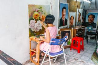 A freelance artist painting a replica in one of the alleyways