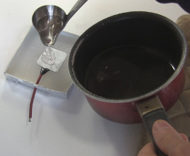 Pouring melted wax into a capacitor mold