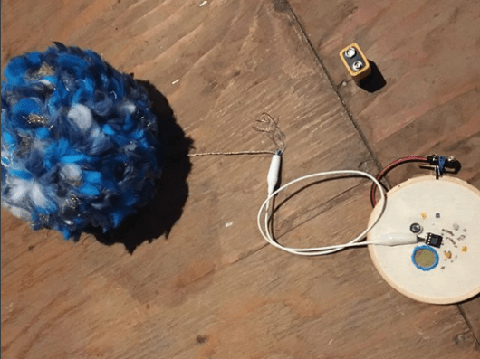 Sewn FM transmitter circuit with pom-pom antenna. Created by Sam Topley. Photo by Teresa Lamb.