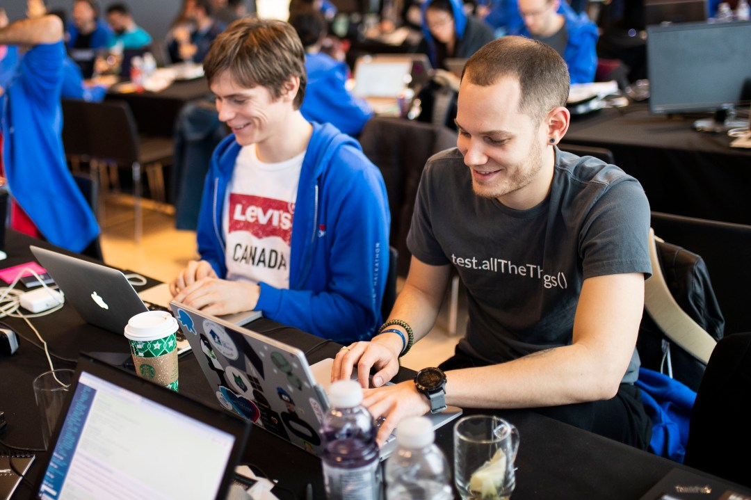 Two men working on laptop at Capital One hackathon