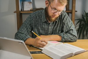 Man studerar en bok och skriver anteckningar.