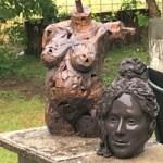 Två keramikalster i trädgården, en torso och ett huvud.