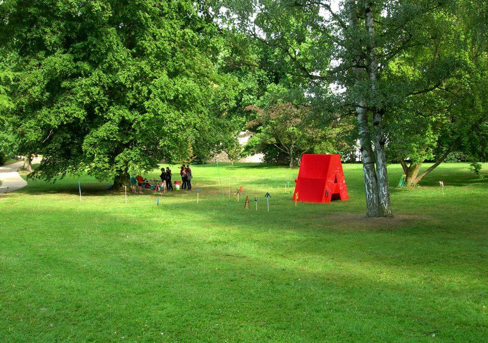 """Das """"Worthaus"""" im Schlosspark, umgeben von kleinen Buchstaben."""