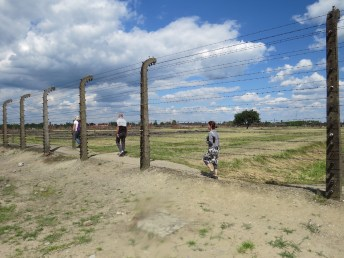 Students walk along one of the fences at Birkenau