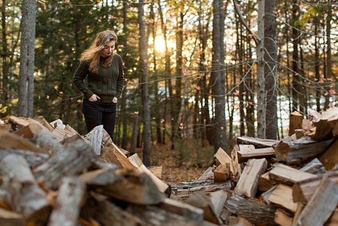 A senior portrait of a girl standing behind a wood pile.
